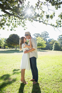 Attractive couple standing and embracing in parkの写真素材 [FYI00002008]