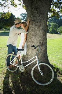 Cute couple leaning against tree in the parkの写真素材 [FYI00002011]