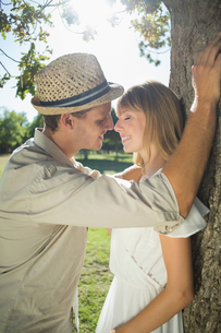 Cute couple leaning against tree in the parkの写真素材 [FYI00002014]