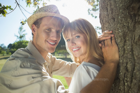 Cute couple leaning against tree in the park smiling at cameraの写真素材 [FYI00002015]