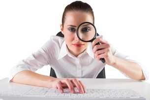 Businesswoman typing and looking through magnifying glassの写真素材 [FYI00002017]