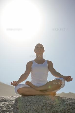 Blonde woman sitting in lotus pose on beachの素材 [FYI00002040]
