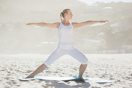 Calm woman standing in warrior pose on beachの素材 [FYI00002044]
