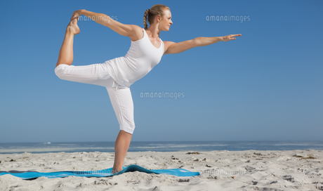 Blonde woman standing in warrior pose on beachの素材 [FYI00002045]
