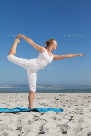 Blonde woman standing in warrior pose on beachの素材 [FYI00002051]