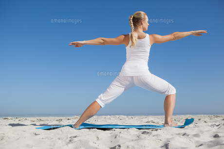 Calm woman standing in warrior pose on beachの素材 [FYI00002052]