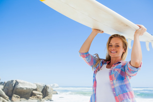 Blonde surfer holding her board smiling at cameraの素材 [FYI00002054]
