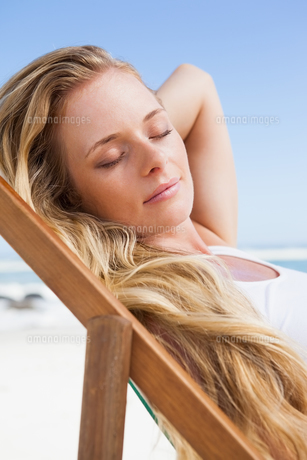 Gorgeous blonde sitting at the beach with eyes closedの写真素材 [FYI00002057]