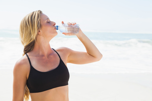 Fit blonde drinking water on the beachの素材 [FYI00002059]
