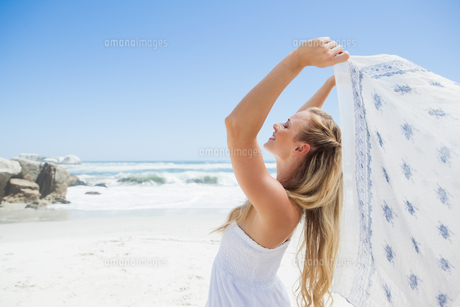 Pretty carefree blonde posing on the beach with scarfの写真素材 [FYI00002060]