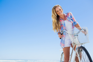 Pretty blonde on a bike ride at the beach smiling at cameraの素材 [FYI00002061]