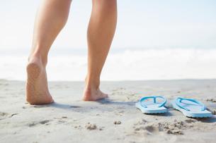 Female feet stepping on sand beside flip flopsの素材 [FYI00002064]