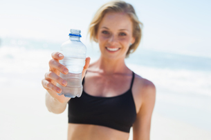 Fit blonde drinking water on the beachの素材 [FYI00002065]