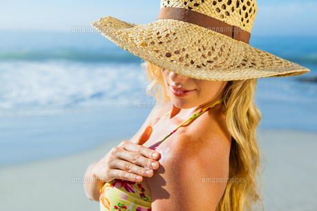 Gorgeous blonde in bikini applying suncream on the beachの素材 [FYI00002069]