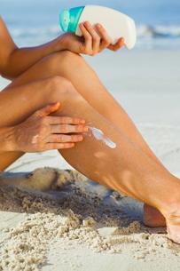 Woman sitting on the beach applying suncreamの写真素材 [FYI00002071]