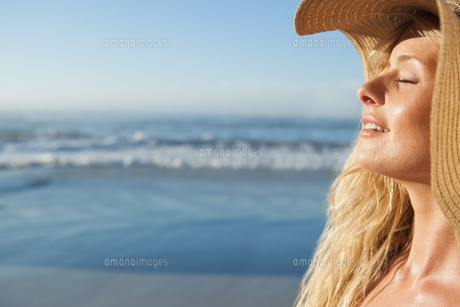 Gorgeous blonde in straw hat smiling on beachの素材 [FYI00002072]