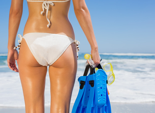 Fit woman in white bikini holding snorkeling gear on the beachの素材 [FYI00002073]
