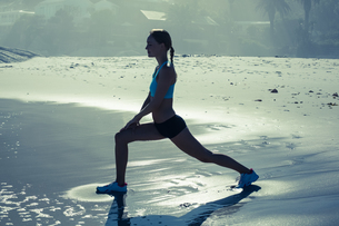 Fit woman doing lunges on the beachの写真素材 [FYI00002077]