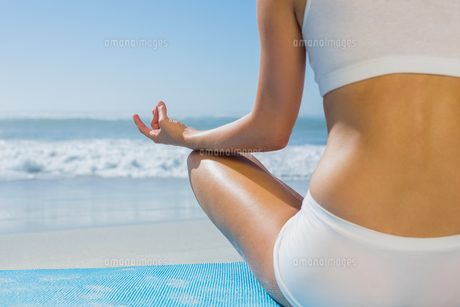 Fit woman sitting in lotus pose on the beachの素材 [FYI00002080]
