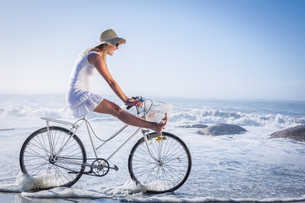 Gorgeous happy blonde on a bike ride at the beachの素材 [FYI00002084]