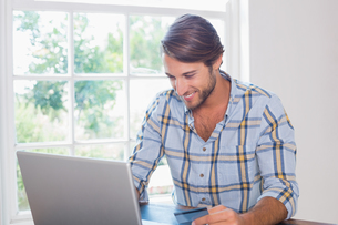Smiling casual man using laptop to shop onlineの写真素材 [FYI00002086]
