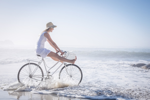 Gorgeous happy blonde on a bike ride at the beachの写真素材 [FYI00002089]