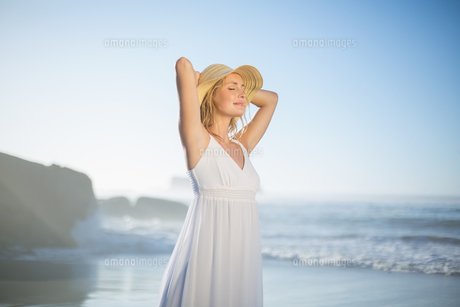 Smiling blonde standing at the beach in white sundress and sunhatの素材 [FYI00002092]
