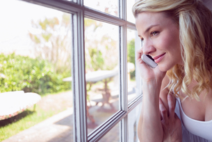 Pretty blonde sitting by the window on a phone callの素材 [FYI00002096]