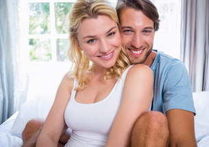 Cute young couple relaxing on bed smiling at cameraの写真素材 [FYI00002099]
