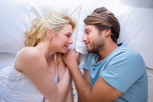 Cute couple relaxing on bed smiling at each otherの写真素材 [FYI00002100]