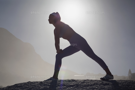 Sporty blonde stretching on the beach on a rockの素材 [FYI00002126]