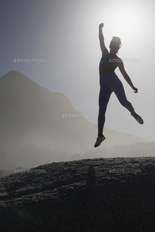 Sporty blonde on the beach on a rock jumpingの写真素材 [FYI00002129]