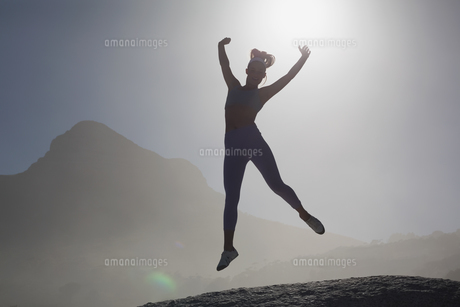 Sporty blonde on the beach on a rock jumpingの写真素材 [FYI00002130]