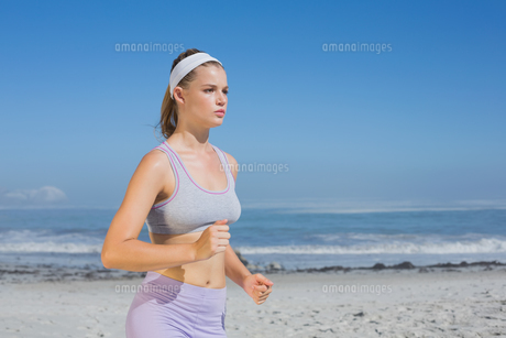 Sporty focused blonde jogging on the beachの写真素材 [FYI00002132]