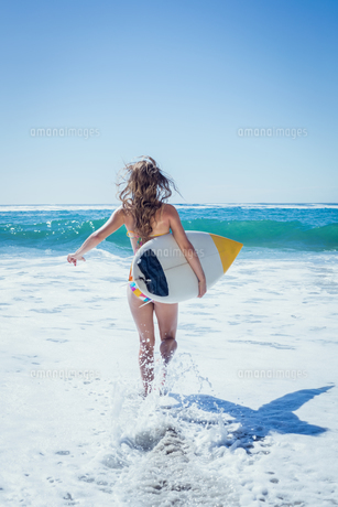 Fit surfer girl running to the sea with her surfboardの写真素材 [FYI00002133]