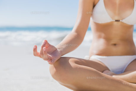 Girl in white bikini sitting in lotus pose on beachの素材 [FYI00002135]