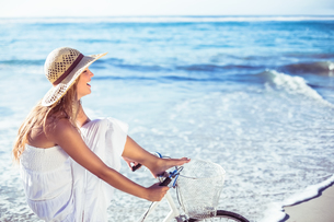 Beautiful blonde in white sundress on bike ride at the beachの写真素材 [FYI00002138]