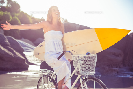 Beautiful surfer in sundress on bike holding surfboard at the beachの素材 [FYI00002139]