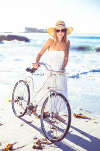Beautiful smiling blonde in sundress with her bike at the beachの写真素材 [FYI00002140]