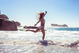 Beautiful smiling woman in white bikini skipping on the beachの素材 [FYI00002141]