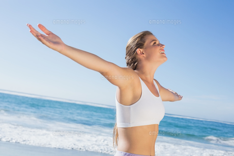 Sporty blonde standing on the beach with arms outの写真素材 [FYI00002142]