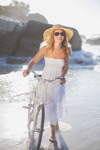 Beautiful smiling blonde in sundress with her bike at the beachの写真素材 [FYI00002143]