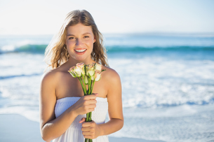 Beautiful blonde in sundress holding roses on the beachの写真素材 [FYI00002146]