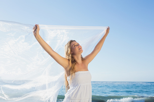 Beautiful calm blonde in white sundress on the beach with scarfの素材 [FYI00002148]
