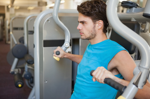 Focused man using weights machine for armsの写真素材 [FYI00002150]