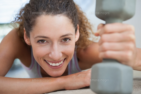 Fit woman smiling at camera holding dumbbellの写真素材 [FYI00002152]