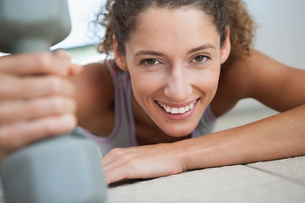 Fit woman smiling at camera holding dumbbellの写真素材 [FYI00002157]