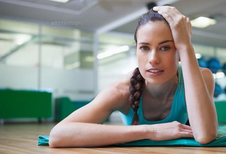 Fit tired brunette lying on studio floorの写真素材 [FYI00002160]