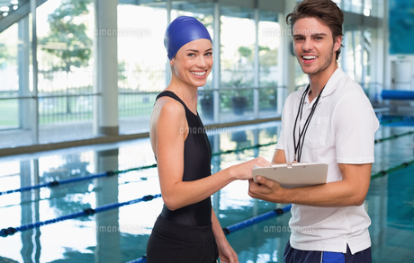 Swimmer smiling at camera with her coach by the poolの写真素材 [FYI00002165]