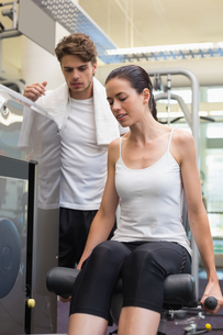 Fit brunette using weights machine for legs with trainer watchingの写真素材 [FYI00002166]